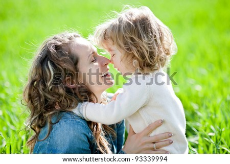 Happy family having fun in spring field against natural green background - stock photo