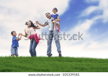 Happy family having fun in summer day  shot in meadow - stock photo