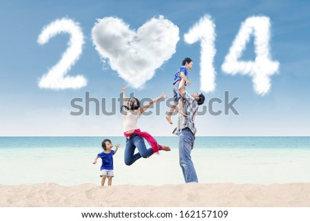 Happy family having fun in the beach with heart shaped cloud of new year 2014 - stock photo