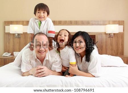 Happy family having fun in the bedroom - stock photo