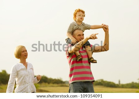 happy family having fun in the field with yellow flowers and watching up in the sky. father pointing something ahead. outdoor shot - stock photo