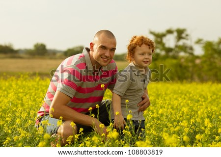 happy family having fun in the field with yellow flowers. Father and his son. outdoor shot - stock photo