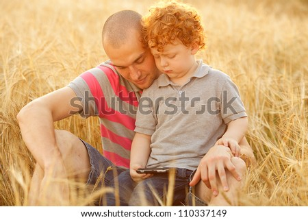 happy family having fun in the field with yellow flowers. Father hugs his son. dad and son looking at mobile device. outdoor shot - stock photo