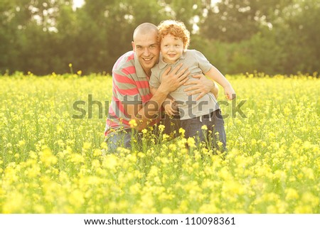 happy family having fun in the field with yellow flowers. Father hugs his son. outdoor shot