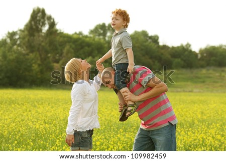 happy family having fun in the field with yellow flowers. Mother holding baby's hand. outdoor shot - stock photo