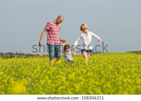 happy family having fun in the field with yellow flowers. outdoor shot - stock photo