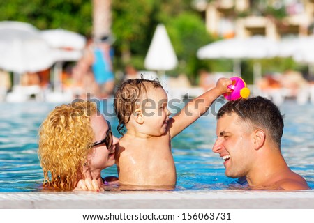 Happy family having fun in the pool - stock photo