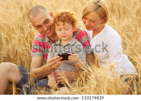 happy family having fun in the wheat field. Father and mother behind their son. Son watching something in dad's mobile (cell) phone. outdoor shot - stock photo