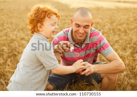 happy family having fun in the wheat field. Father doing soap bubbles to his son. - stock photo