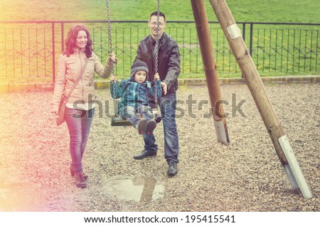 Happy family having fun on children's playground