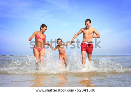 happy family having fun on the beach - stock photo