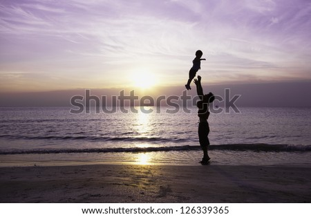 Happy family having fun on the beach,Father and son play on the Beach in sunrise silhouette shot - stock photo