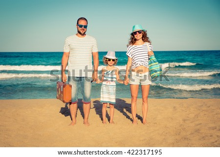 Happy family having fun on the beach. Summer vacation and travel concept - stock photo