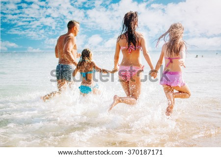 Happy family having fun on the beach. They with holding hands running and splashing in the sea. - stock photo