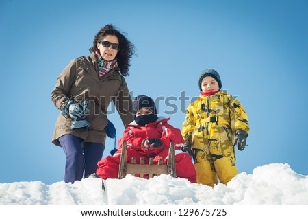 Happy family having fun on the snow with sled. - stock photo