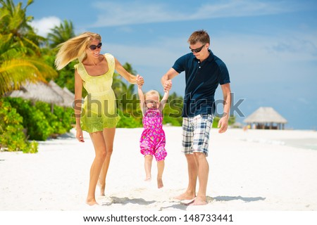 Happy family having fun on the white sandy beach at Maldives - stock photo