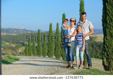 Happy family having fun on vacations in Tuscan against cypress alley background - stock photo