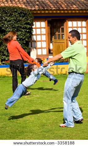 happy family having fun outdoors at home - parents making kids go round in the air - stock photo