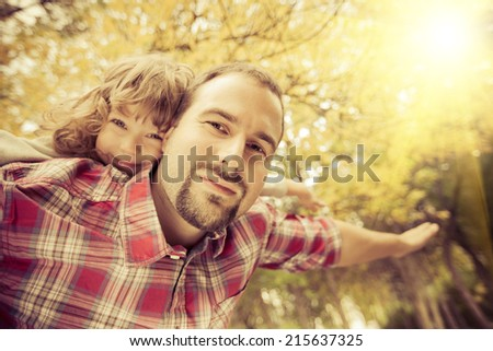 Happy family having fun outdoors in autumn park against yellow blurred leaves background - stock photo