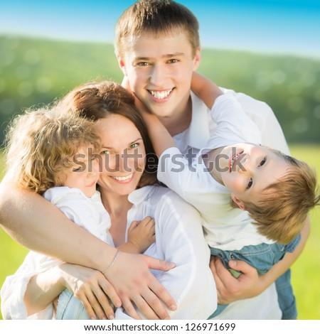 Happy family having fun outdoors in spring field - stock photo