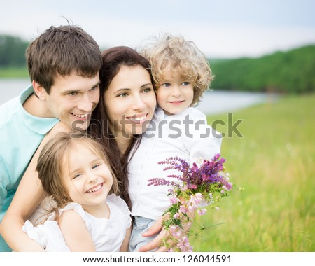 Happy family having fun outdoors in spring field against blurred grass and sky background - stock photo