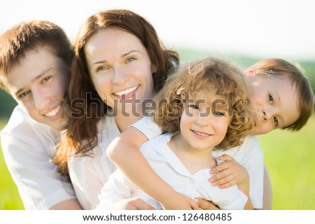 Happy family having fun outdoors in spring field against natural green background - stock photo
