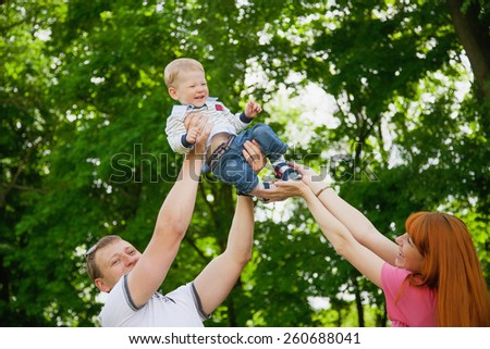 Happy family having fun outdoors in spring garden. Father, mother and child. Family concept. Picnic. Woman, man holding little boy in hands. Laughing, smiling people playing with son - stock photo