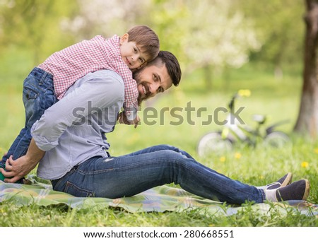 Happy family having fun outdoors in spring garden. Father playing with child. Family concept. - stock photo