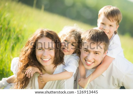 Happy family having fun outdoors in spring green field - stock photo