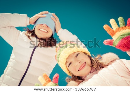 Happy family having fun outdoors in winter against blue sky background. Low angle view selfie - stock photo