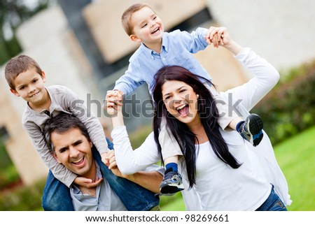 Happy family having fun running outdoors and smiling - stock photo