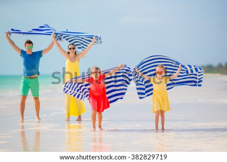 Happy family having fun running with towel and enjoying vacation on tropical beach with white sand and turquoise ocean water - stock photo