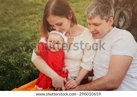 happy family having fun together on the walk with baby daughter in summer park - stock photo