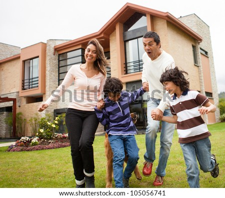 Happy family having fun together running outdoors - stock photo