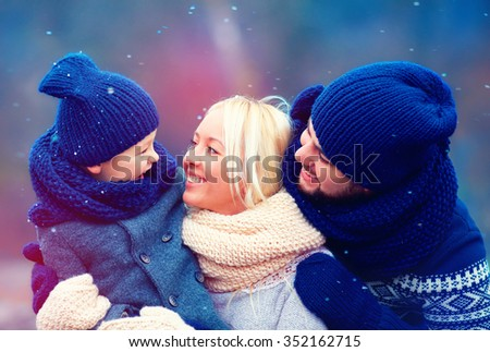 happy family having fun together under winter snow - stock photo