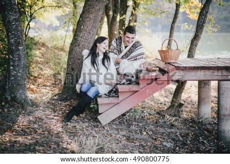 Happy family having great time in a forest near lake. Autumn mood