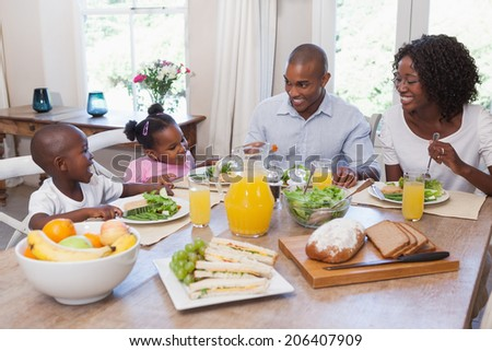 Happy family having lunch together at home in the kitchen - stock photo