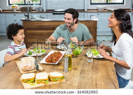 Happy family having lunch together in kitchen at home - stock photo