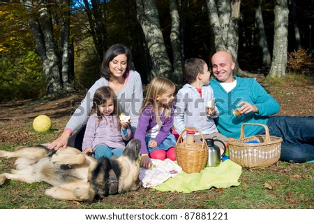 Happy family having picnic in autumn - stock photo