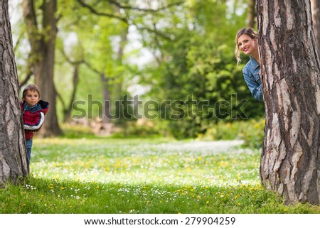 Happy family hiding behind trees while playing in a park - stock photo