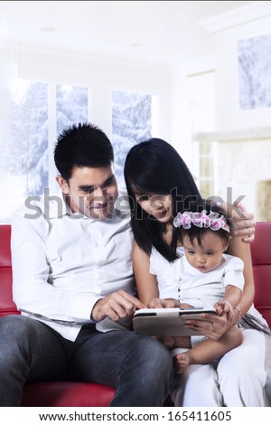 Happy family holding a digital tablet sitting on red couch