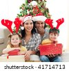 Happy family holding Christmas gifts at home - stock photo