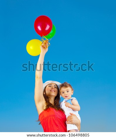Happy family holding colorful air balloons over blue sky background, mother and adorable child baby boy playing games outdoor, mum and kid having fun in summer nature, hands up, freedom joy concept - stock photo