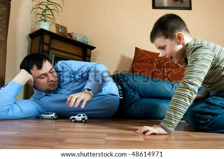 happy family home: father and son playing on the floor - stock photo