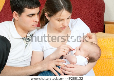 happy family home: father, mother and baby sitting on the floor in living room - stock photo