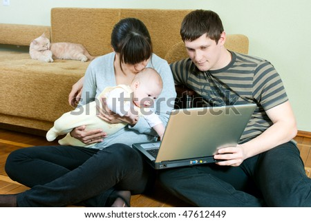 happy family home: father, mother and baby working on laptop