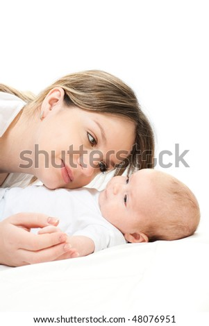 happy family home: mother and baby lying on the bed and playing
