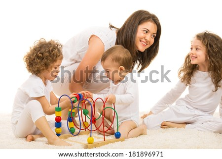Happy family home,two kids playing with a wooden toy in front of image and mother having fun and conversation with one of daughter - stock photo