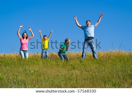 Happy family hopping in the field - stock photo