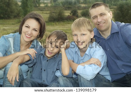 happy family in a blue shirts resting on nature